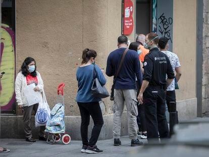 Cola de usuarios de la oficina de servicios sociales del Raval de Barcelona, el verano pasado.