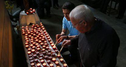 Dos asistentes encienden velas durante la misa celebrada en Digne-les-Bains.