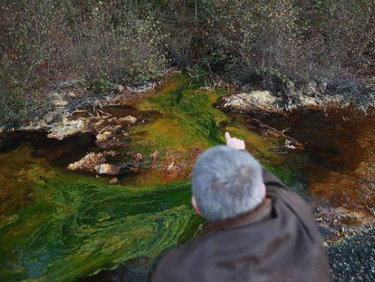 Un vecino de Touro muestra el drenaje ácido de mina en el agua de la zona.