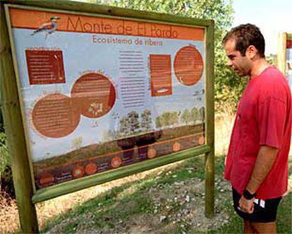 Un excursionista, ante un panel explicativo con las rutas propuestas para la observación de aves en El Pardo.