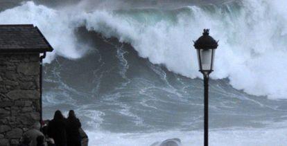 Varios turistas graban las olas este jueves en la costa de Muxía (A Coruña).