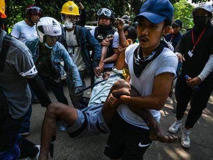 Varios manifestantes transportan a un herido durante la represión violenta en Yangón este viernes.