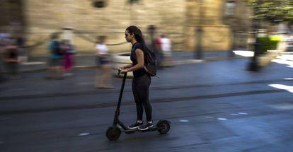 Una joven conduce un patinete eléctrico por el centro de Sevilla.
