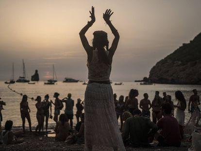 Una mujer baila al atardecer en la cala Benirrás de Ibiza.