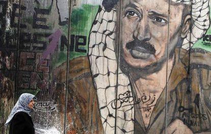 Una mujer camina frente a un mural con el rostro del fallecido líder palestino Yasir Arafat, en Ramala.