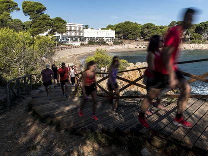 Turistas por el Camino Ronda de la Playa de El Portitxol en l'Escala, con el Hostal Spa Empúries al fondo.