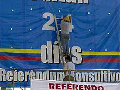 Un voluntario cambia el número de los días que quedan para la votación.