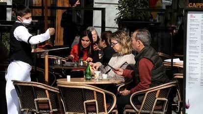 Una camarera atiende a varios clientes en una terraza de un bar de Madrid.