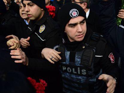 Agentes de policía controlan el acceso al club Reina de los ciudadanos que quieren depositar flores en homenaje tras el atentado.