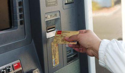 Una mujer saca dinero de un cajero automático.