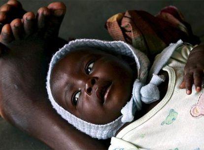 Un pequeño espera tumbado sobre las piernas de su madre para recibir atención médica en el centro de investigación sobre la malaria de Manhiça (Mozambique).