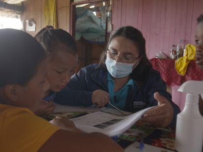 Adriana López da clase a Michelle en su casa, en presencia de sus hermanos, en Cascales (Sucumbíos, Ecuador).