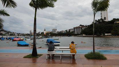 Dos personas sentadas en una banca en Acapulco, Guerrero, este lunes.