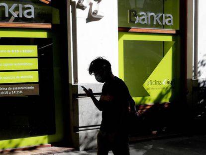 Una persona camina por el centro de Madrid delante de una sucursal de Bankia.