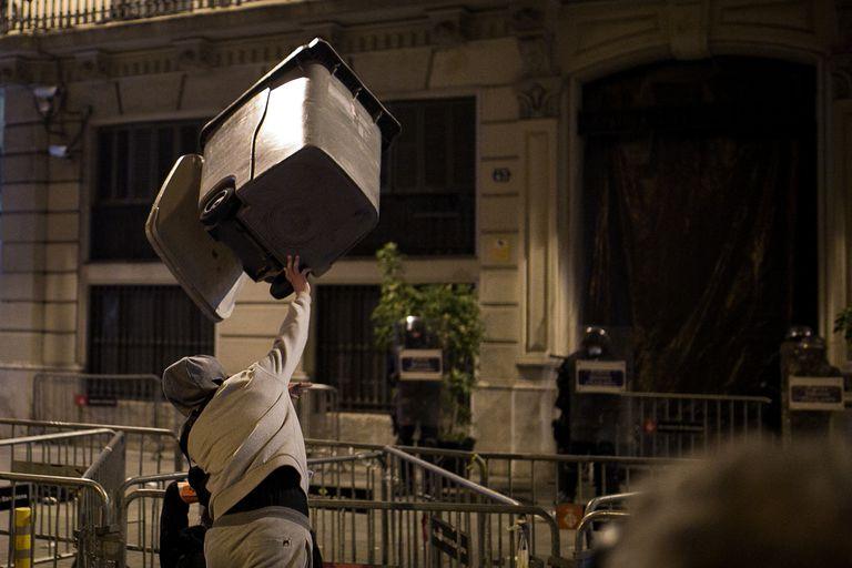 Un joven lanza un contenedor contra agentes antidisturbios de los Mossos este domingo en Barcelona.