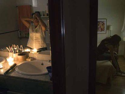 Una vecina de Congres-Indians se peina en el baño de su casa a la luz de varias velas