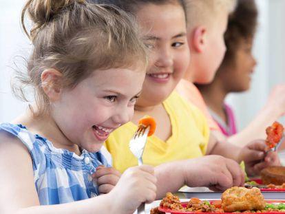 Happy school children enjoying their school dinners