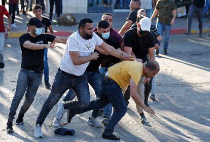 La policía palestina vestida detuvo a un manifestante en Ramallah el domingo.