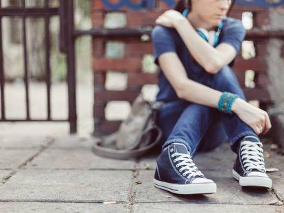 Una joven se sienta en la puerta del colegio.