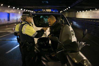 Un agente hace la prueba de alcoholemia a un motorista.