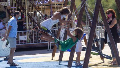 Unas niñas juegan en unos columpios junto al Ayuntamiento de San Sebastián, este viernes.