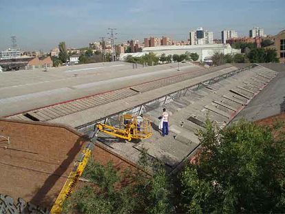 Desmontaje de placas de tejado con amianto en una nave industrial.