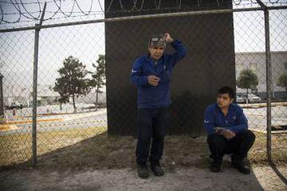 Dos obreros de Carrier, fumando junto a la planta.