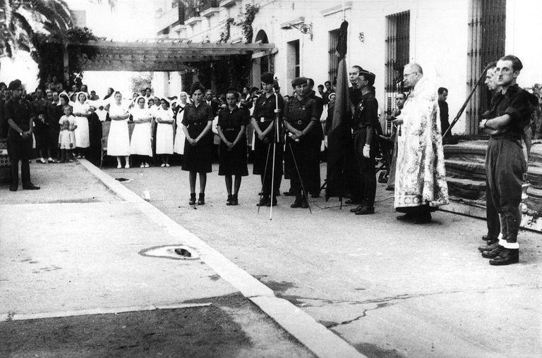 Entrega de una bandera nacional en un acto de Falange de Badajoz, durante la Guerra Civil.
