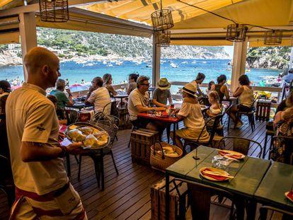 Un camarero lleva una bandeja con pescado fresco en el chiringuito-restaurante Toc al Mar, en la cala de Aiguablava, en Girona.