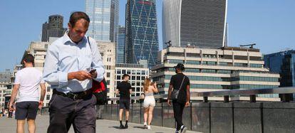 Un hombre utiliza su teléfono móvil, mientras que una mujer toma una fotografía con su smartphone en el London Bridge de la capital británica.