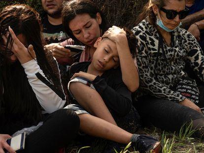 Una madre venezolana abanica a su hijo tras cruzar el Río Bravo.