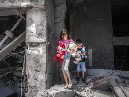 Niños palestinos rescatan juguetes de su casa, que resultó gravemente dañada por los ataques aéreos israelíes, en la Torre Al-Jawhara en Gaza, el pasado 17 de mayo.