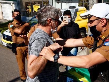 Un manifestante forcejea con un policía ante la comisaria donde Moro testifica contra Bolsonaro este sábado en Curitiba.