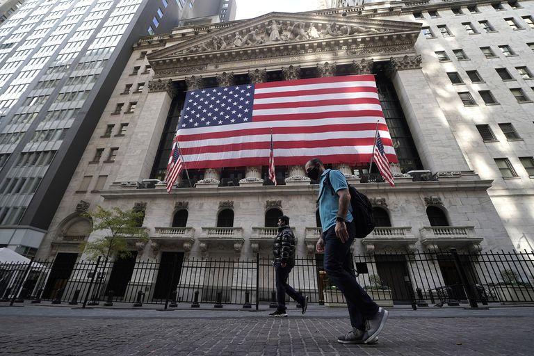Dos personas pasan este viernes por la Bolsa de Nueva York.