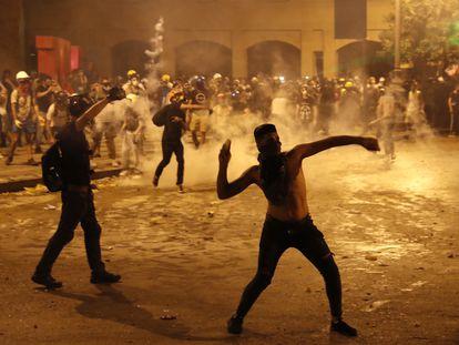 Un manifestante lanza piedras contra la policía antidisturbios libanesa, en Beirut. En vídeo, nueva jornada de enfrentamientos en Beirut.