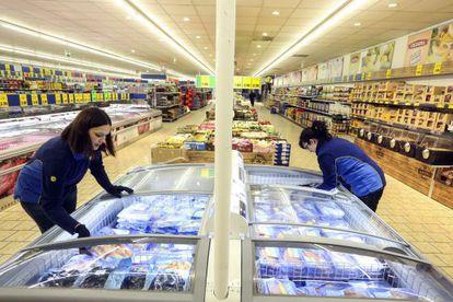 Dos empleadas reponen productos en las neveras de un supermercado de Lidl en Madrid