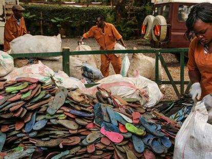 Empleados de Ocean Sole abren sacos con chancletas usadas procedentes de Nairobi y la costa de Kenia.