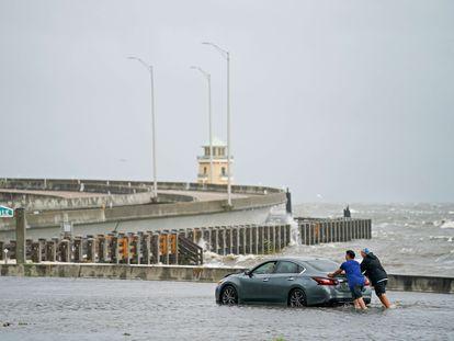 Dos hombres ayudan a un conductor varado en las inundaciones del 30 de agosto de 2021 en Biloxi, Mississippi.