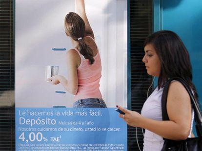 Una mujer pasa frente al anuncio de un depósito bancario, en 2019.
