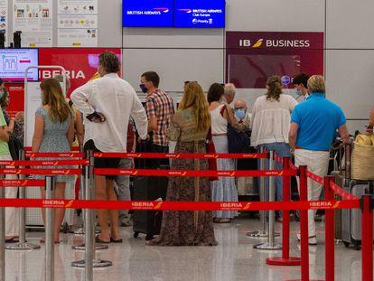 Viajeros con destino al Reino Unido hacen cola para facturar en el aeropuerto de Palma de Mallorca, este domingo.