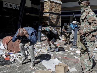 Un militar vigilaba a varios hombres detenidos por saqueo, en un centro comercial de Soweto, el 13 de julio.