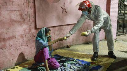 Una mujer sin hogar recibe alimentos de un grupo de voluntarios durante el confinamiento por la covid-19 en Bangladés en 2020.