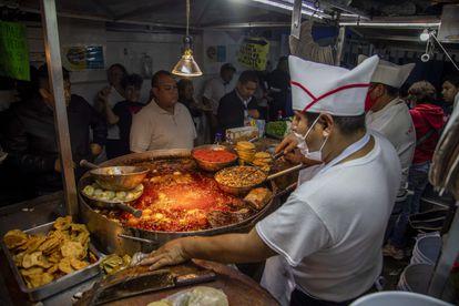Personas esperan en un negocio de comida donde se preparan tacos para llevar, en septiembre pasado.