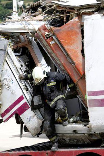 Un bombero trabaja en uno de los vagones del tren siniestrado en Santiago.