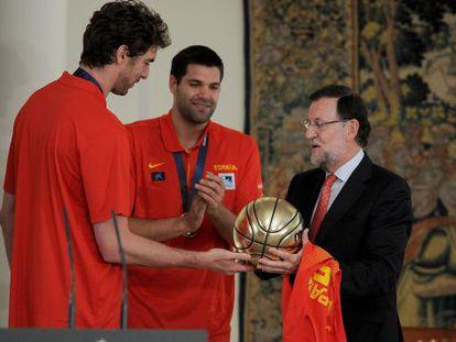 Gasol, a la izquierda, regala al presidente del Gobierno, Mariano Rajoy, un balón de plata en La Moncloa tras la victoria en el Eurobasket.