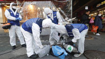 Un grupo de trabajadores rocía desinfectante en un mercado de Seúl este lunes.