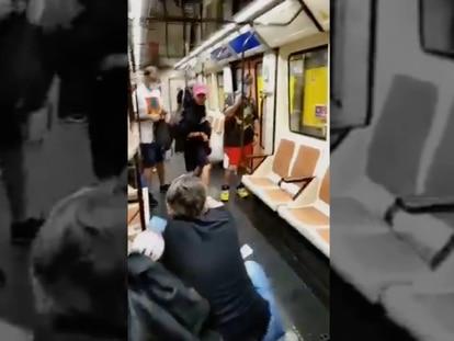 Imagen del vídeo grabado por un pasajero en el que se ve al enfermero arrodillado y al agresor con la gorra rosa.