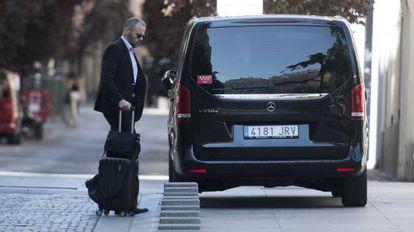 Un vehículo VTC, recoge a un viajero en Madrid.