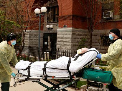 Personal sanitario trasladan a un anciano de una residencia de Brooklyn (Nueva York) por un brote de coronavirus, el 17 de abril de 2020.