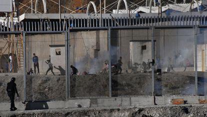 Varios ciudadanos marroquíes lanzan piedras en la frontera del Tarajal, en Ceuta, este miércoles.